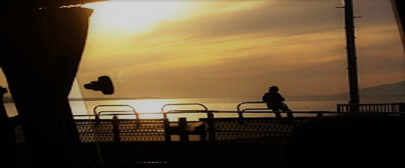 海辺の夕陽にたたずむ人の影